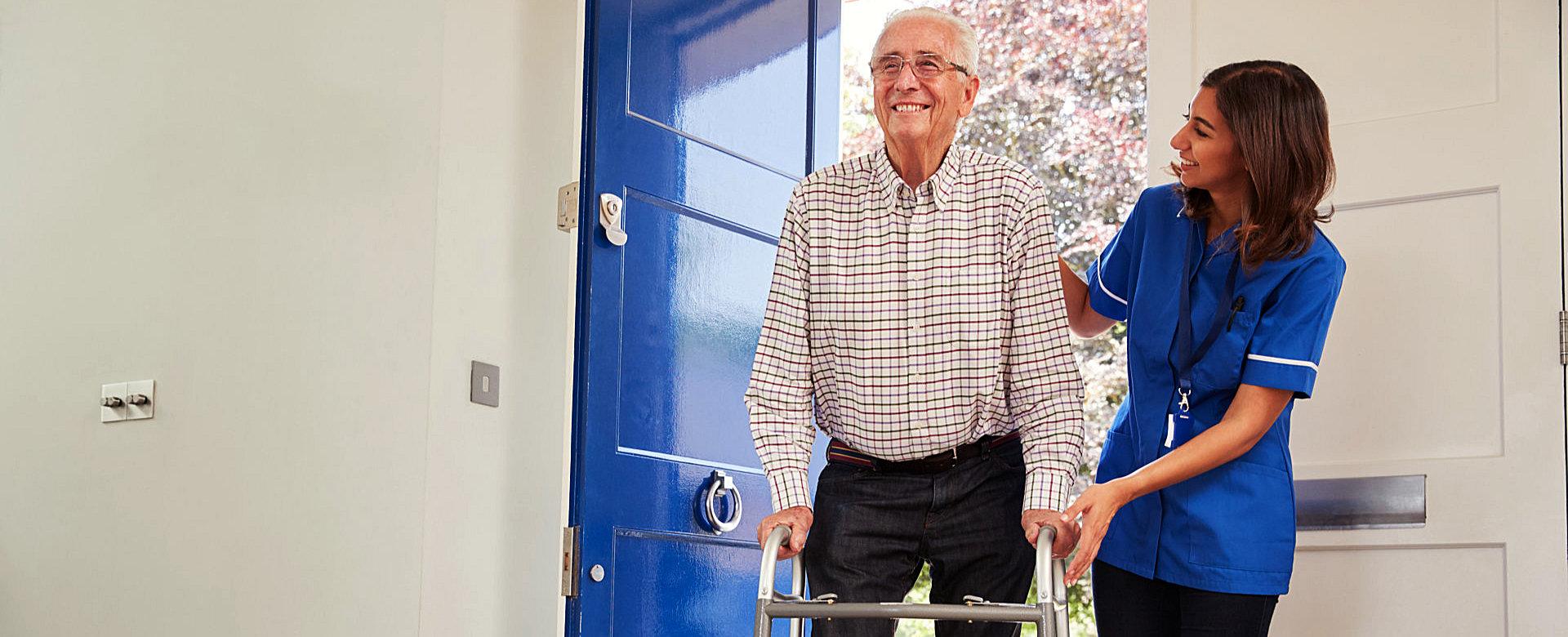 a pharmacist assisting a senior man walk