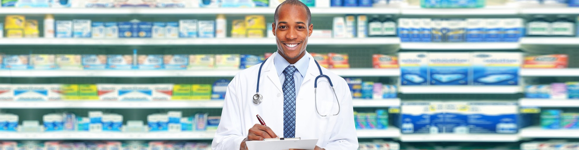 a pharmacist smiling, medicine stocks in the background